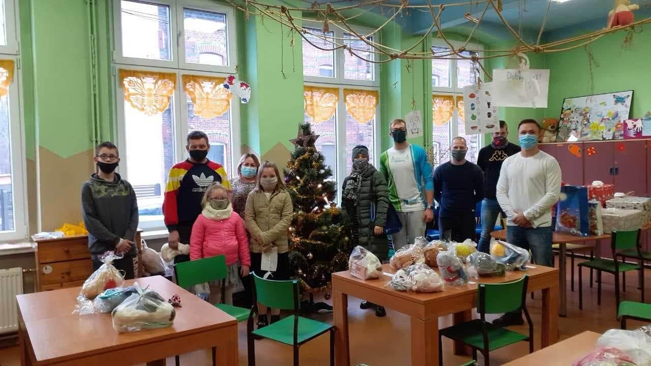 Darczyńcy razem z dziećmi i Kierownikiem Ośrodka przy choince w świetlicy OIK